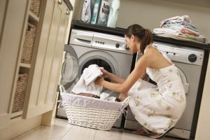 Woman loading her washing machine.