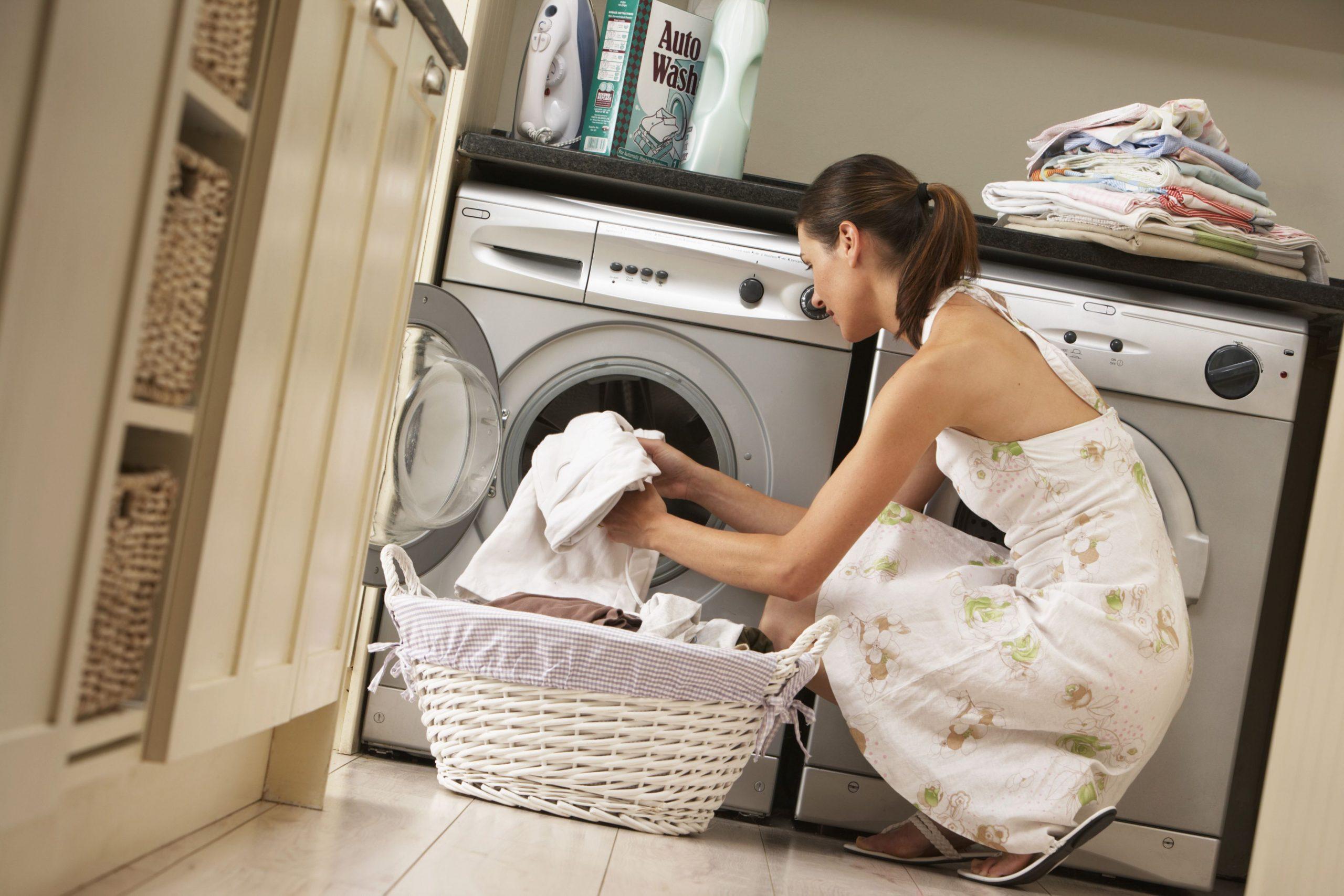 Woman loading her washing machine.